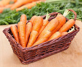 Fresh carrots in a basket on the table — Stock Photo