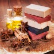 Handmade soap, oil in bottles anise and cinnamon on the table — Stock Photo