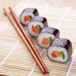 Delicious fresh sushi rolls on the mat — Stock Photo #27422897