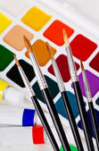 A set of brushes on the background of acrylic and watercolor — Stock Photo