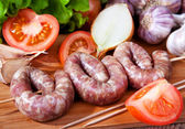 Sausage, garlic, tomatoes, lettuce, onions — Stock Photo