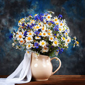 Chamomile and cornflowers. Flowers in a vase on the table — Stock Photo
