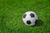 New soccer ball on green grass — Stok fotoğraf