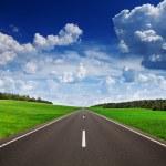 Asphalt road in green fields under beautiful sky — Stock Photo