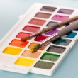 watercolor paints and brush on the table — Stock Photo #32873131