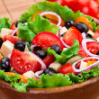 Delicious and healthy salad in a wooden bowl — Stock Photo