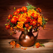 Still life with autumn flowers on a table in a copper vase — Stock Photo #34250749