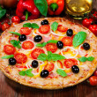 Tasty pizza and fresh ingredients on the table — Stock Photo
