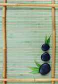 Bamboo frame and black stones — Stock Photo