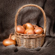 Stock Photo: Beautiful and ripe onions in basket on table