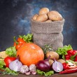Potatoes in a bag and vegetables on a wooden table — Stock Photo