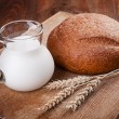 Bread and milk in a glass jar on a wooden table — Stock Photo