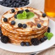 Fresh pancakes with berries and honey — Stock Photo