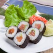 Salmon and caviar rolls and salad served on a plate — Stock Photo #36990607