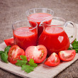 Tomato juice in glass and sliced tomatoes on a fabric — Stock Photo