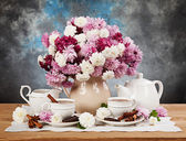 Chrysanthemums in a vase on a wooden table — Stock Photo