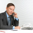Cheerful young business man using mobile phone at desk — Stock Photo #12589281