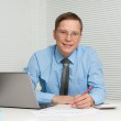 Young businessman smiling at his desk in a office — Stock Photo #12696984