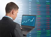 Businessman with laptop on Stock Market Background — Stock Photo