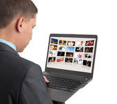 Man looking some pictures on the laptop — Stock Photo