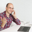 Royalty-Free Stock Photo: Happy young man at office, working on laptop computer, smiling.