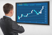 Businessman checking stock market on monitor — Stock Photo