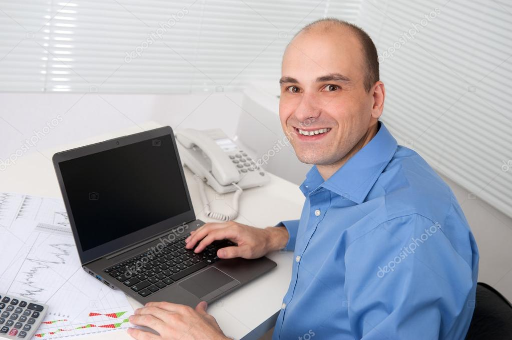 Portrait of relaxed young business man with laptop sitting in office chair — Stock Photo #13861278