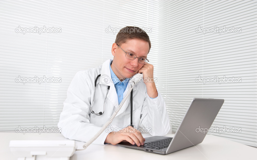 Male doctor working on a laptop — Stock Photo #13861284