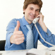Smart happy business man at office desk using phone — Stock Photo #14815585