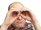 Man looking through binoculars from arms — Stock Photo