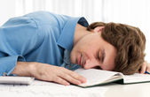 Business man resting head on notebook — Stock Photo