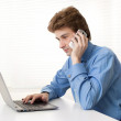 Man talking on phone in front of the laptop — Stock Photo #19695149