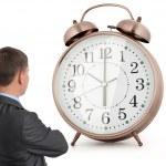 ビジネス男が目覚まし時計を見て — ストック写真
