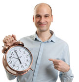 Smiling guy pointing on a big alarm clock — Stock Photo