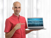Man pointing on fast delivery logo on his Laptop — Stock Photo