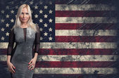 Beautiful blonde woman over Grunge USA Flag background — Stock Photo