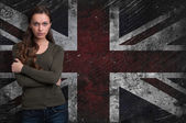 Beautiful girl over Grungy UK Flag background — Stock Photo