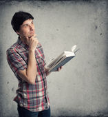 Thoughtful mid adult man with book looking up — Stock Photo