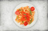 Fusilli pasta with tomato sauce and arugula — Stock Photo