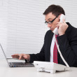 Businessman speaking on phone, sitting at desk, looking at lapto — Stock Photo