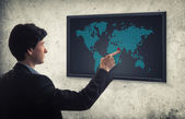 Businessman pushing world map interface — Stock Photo