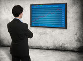 Man looking on the screen with stock market graph — Stock Photo