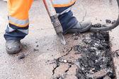 Road worker breaking street asphalt with jackhammer — Stock Photo