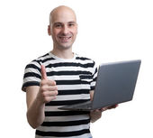 Happy young man in t-shirt working on laptop — Stockfoto