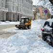 Yellow tractor cleaning the snow on a street — Stock Photo