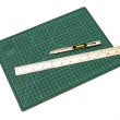 Green cutting mats with iron ruler and cuter isolated on white b — Stock Photo