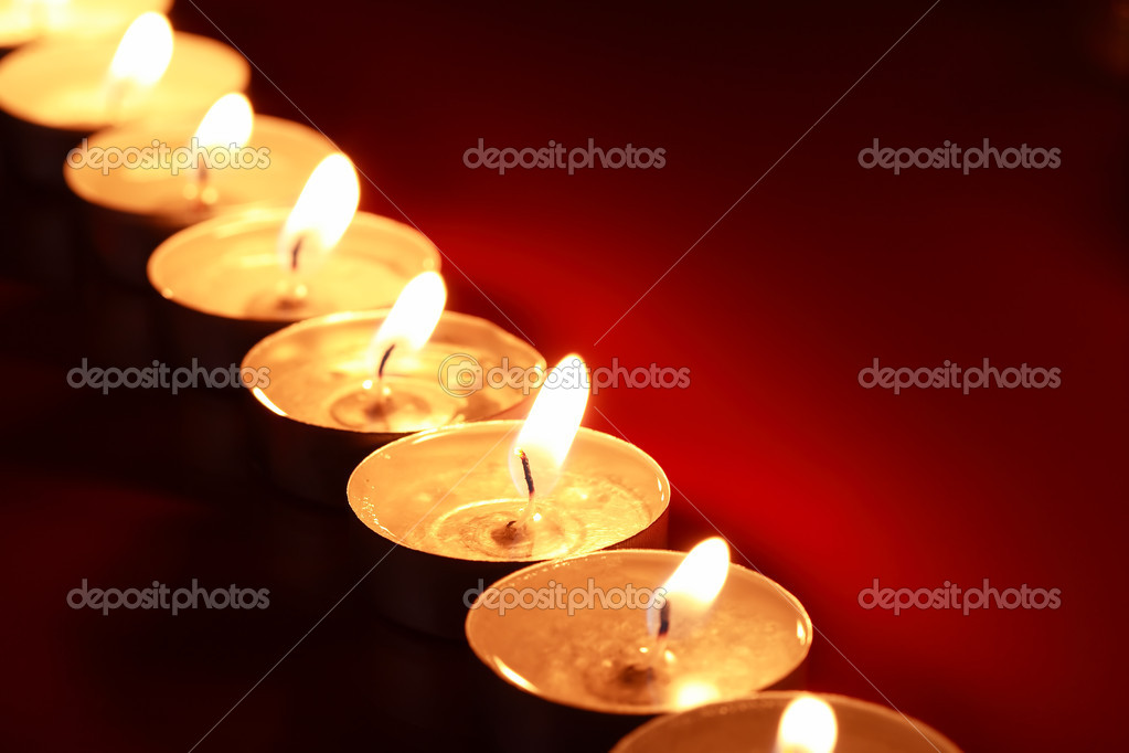 Set of lighting candles in a row on dark red background  Foto Stock #14631557