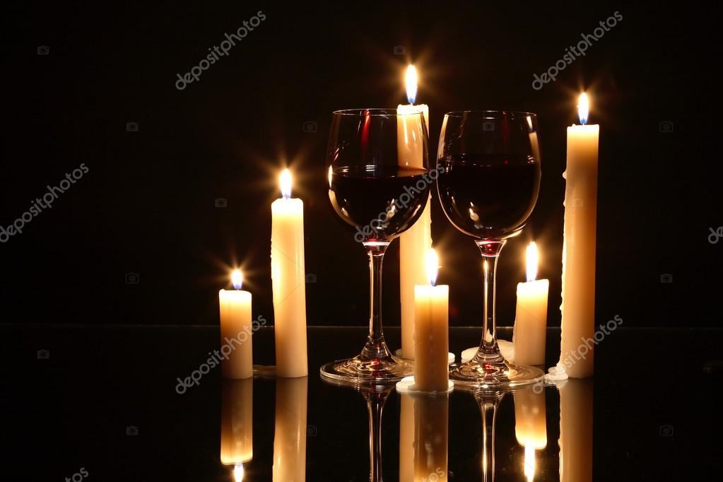 Two elegant goblets of red wine near lighting candles on dark background  Stock Photo #16285243