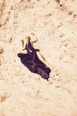 Portrait of attractive woman in sand — Stock Photo