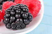 Blackberry and raspberries on white plate — Stock Photo